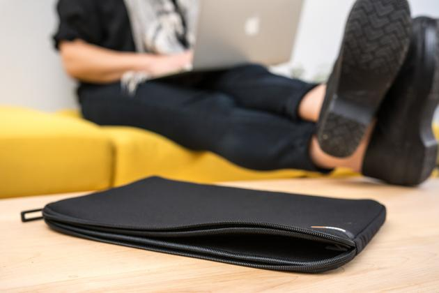 An empty, unzipped AmazonBasics Laptop Sleeve (which is black with rounded corners) sitting on a table, with a person using a MacBook in the background.